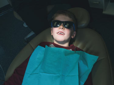 child sitting in dentist chair in Grand Prairie, AB, Canada